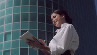 Smiling business woman standing outdoors on a sunny day and working on her tablet
