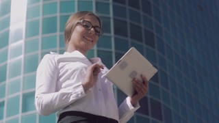Smiling business woman wearing spectacles is working on her tablet