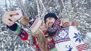 Smiling couple taking their photo in the winter forest