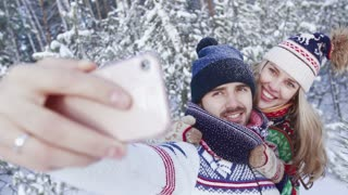 Smiling lovely couple taking selfie in snowbound wood