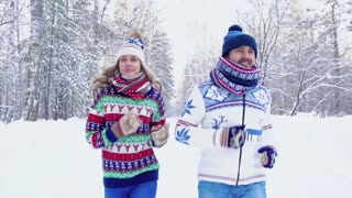 Smiling young woman and handsome young man jogging together in the winter forest
