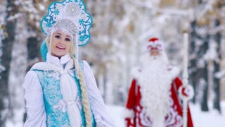 Snegurochka Snow Maiden and Ded Moroz Father Frost meeting in winter forest and waving hands