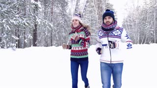 Sportive nice couple jogging in the snowbound forest and enjoying their time