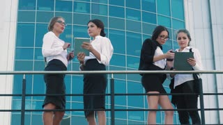 Stylish business women standing on terrace and talking to each other on business topics