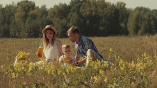 Sunny family eating and drinking in summer field