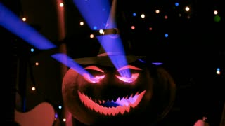 The blue laser light gleams through the Halloween pumpkin