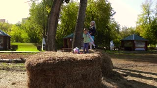 Three active little girls playing in hay and haystacks together