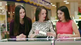 Three attractive women in beautiful dresses looking at accessories in the jewelry store