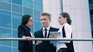 Three coworkers standing on the terrace of office building and talking about their working day and meetings
