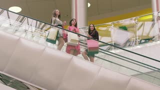 Three female friends in shopping center moving down on escalator