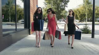 Three glamorous young women walking downtown and showing the purchases