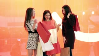Three happy shopping women standing against red background and discussing their purchases