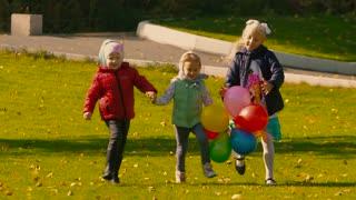 Three little girls having fun on green meadow