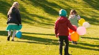 Three little girls picking up the balloons from green and yellow grass