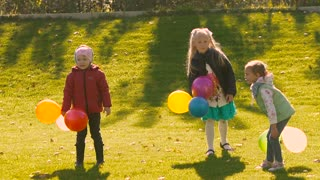 Three little happy girls throwing their colorful balloons to the air