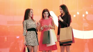 Three shopping women with many shopping bags in hands looking at their purchases