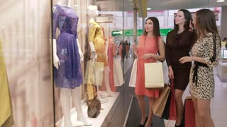 Three smiling friendly women discussing dresses in shopping window while doing shopping