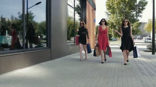 Three wonderful female friends walking down the street and talking to each other