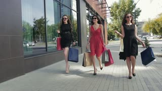 Three young beautiful women enjoying their shopping day together