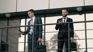 Two attractive and confident businessman holding their briefcases talking on cell phones
