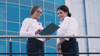 Two attractive business women meeting a business man outdoors