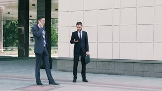Two business men working outdoors at the middle of working day