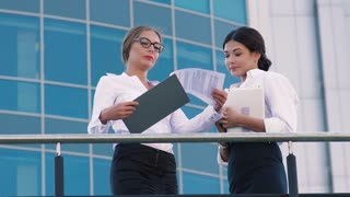 Two business women talking on the terrace, when a business man comes up to them to greet and talk to them