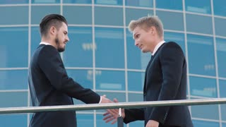 Two confident business men meeting outdoors at the place which they are going to discuss