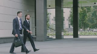 Two confident young businessmen are walking in the urban environment to the office building