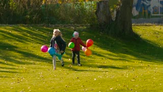 Two cute girls running on green meadow holding colorful balloons
