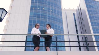 Two female coworkers talking outdoors during lunch time and a man coming out of the business center and talking on the phone