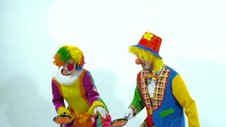 Two funny clowns trying to catch pancakes. Slow motion