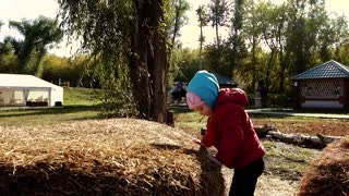 Two girls playing outside on a haystack