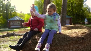 Two little girls sitting on a haystack and throwing hay down