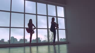 Two lovely women practicing yoga poses together in white studio with natural light