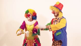 Two playing clowns having fun and trying to blow soap bubbles