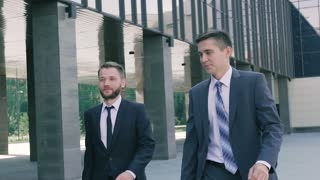 Two smart male coworkers going to work in the day