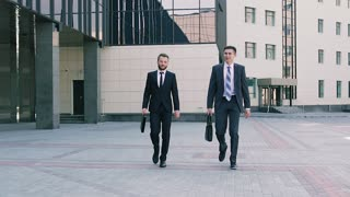 Two stylish business men wearing smart suits walking to the office talking about coming meeting