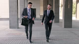 Two young businessmen walking to the office together