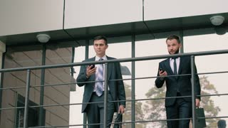 Two young confident businessmen exit the office building talking on the phones