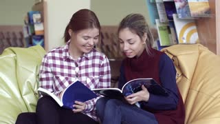 A couple of surprised female students discussing a book