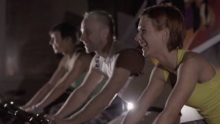 A group of smiling sporty people working out on exercise bikes
