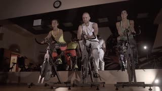 A group of sporty young people working out on stationary bicycles at night