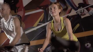 Athletic man and sporty women working out together using stationary bikes