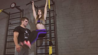 Attractive man and woman athletes performing sit ups. Doing sit ups, stomach muscle definition. Working in pairs. Beautiful young sporty athletic couple doing exercises together