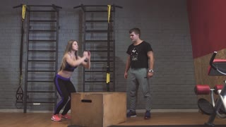 Attractive sports people box jumps while working out in gym