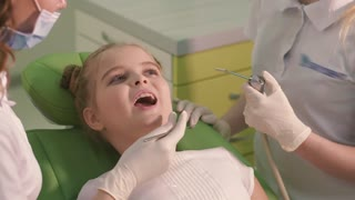 Beautiful and cheerful girl treats the teeth of children dentists. She sits in the dental chair green and smiling.