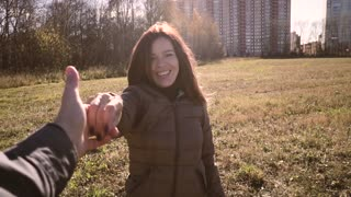Beautiful young couple dancing on the street in the Park. Smile at each other.