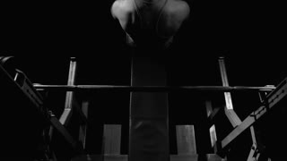 Black-and-white shot of handsome athletic man starting bench pressing