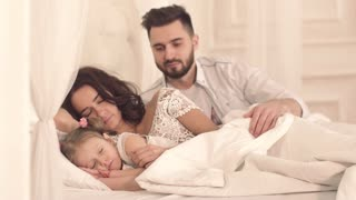 Caring father covering his wife and child with a blanket